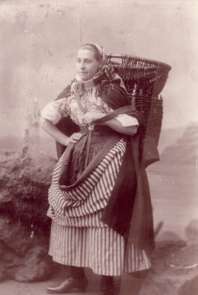 Image of Elizabeth Watson dressed in traditional fishwife clothes carrying basket on her back