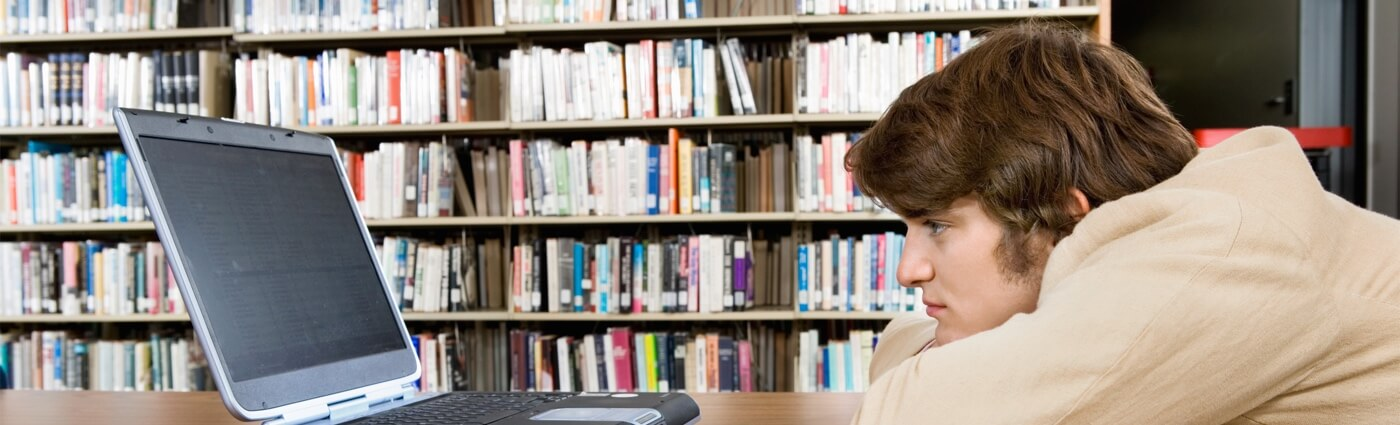 Image of man staring at laptop in library